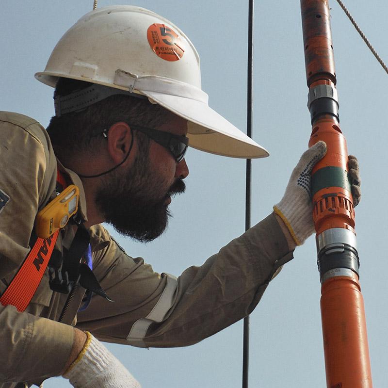 Ingeniero de campo inspeccionando la BES de diámetro reducido SlimLine en el sitio del pozo