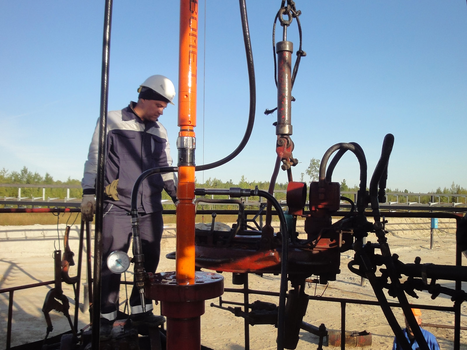 Ingeniero de campo instalando una BES sin torre de perforación por medio de cable Colibri en el sitio del pozo