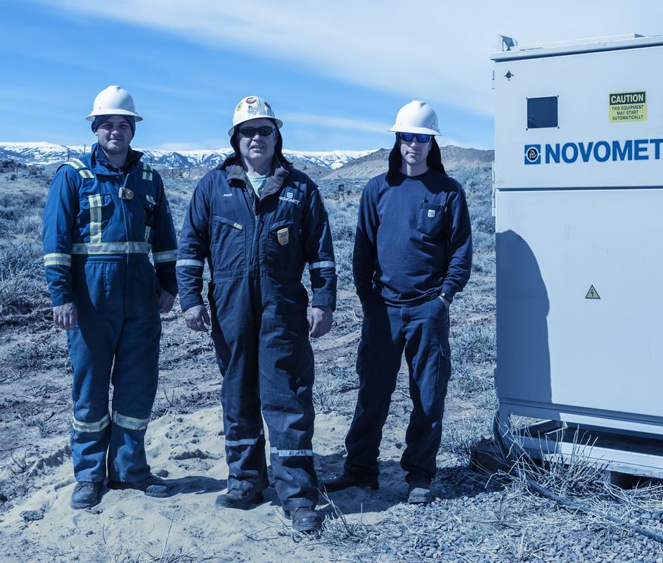 Tres operarios junto a una instalación de variador de velocidad con picos nevados de fondo